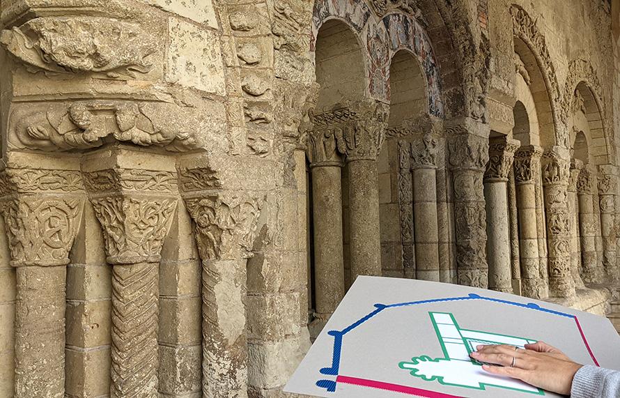 Un visiteur touche une carte en relief face à l'intérieur de l'abbaye Saint-Aubin.